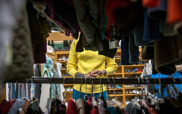 <p>Esperence Batamuriza goes through racks of clothing Oct. 18 at the Saint's Place clothing closet located at St. John of Rochester Church in Fairport.  </p>
