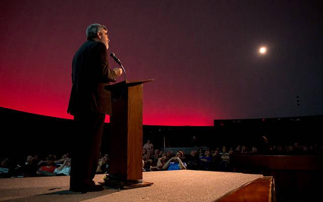 <p>Jesuit Brother Guy Consolmagno speaks before a packed house at the Strasenburgh Planetarium in Rochester Oct. 5.  Courier photo by Jeff Witherow </p>