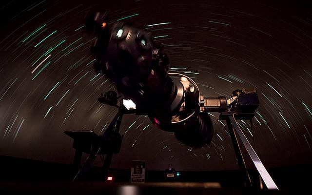 <p>Jesuit Brother Guy Consolmagno concludes his lecture with a viewing of the night sky over Africa using the Strasenburgh Planetarium's star projector.  Courier photo by Jeff Witherow </p>