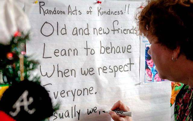 <p>Fourth-grade teacher Annmarie Missell copies a poem about kindness and respect that was written by students as part of the bullying-prevention program at Holy Cross School in Rochester Dec. 16, 2013. (File photo)  </p>