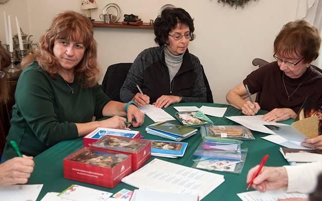 <p>Mary Ann Tombasco (from left), Marge DiMeo and Faye Tong, members of All Saints Parish in Corning, work on Christmas cards Nov. 12 that will be sent to people who are homebound and in local nursing facilities. (Photo by Jason Cox)  </p>