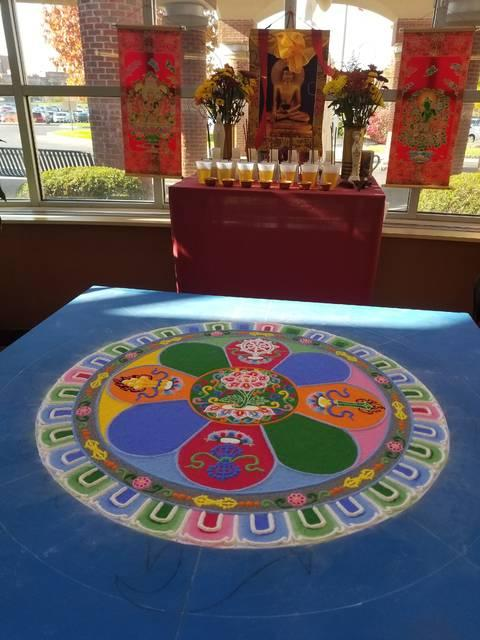 <p>The Venerable Tenzin Yignyen, a Buddhist monk and visiting professor of Tibetan Buddhism at Hobart and William Smith Colleges in Geneva, created a sand mandala in the lobby of St. Ann's Community in early November. (Courier photo by Annette Jiménez)