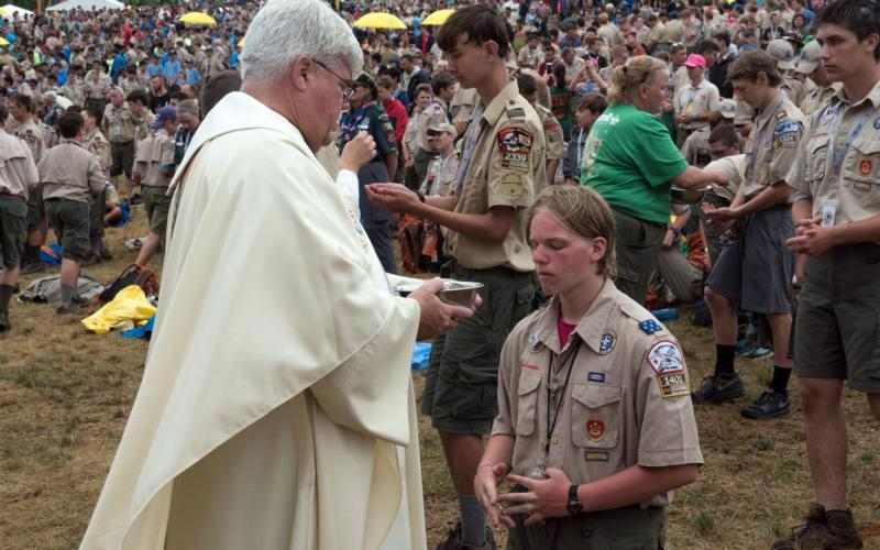 A scout receives Communion during Mass July 23, 2017, at the Boy Scout Jamboree in Glen Jean, W.Va. Scouts frequently combine their love of country with their love of the church when choosing projects in their pursuit of the rank of Eagle Scout. (CNS photo by Michael Roytek, courtesy Boy Scouts of America