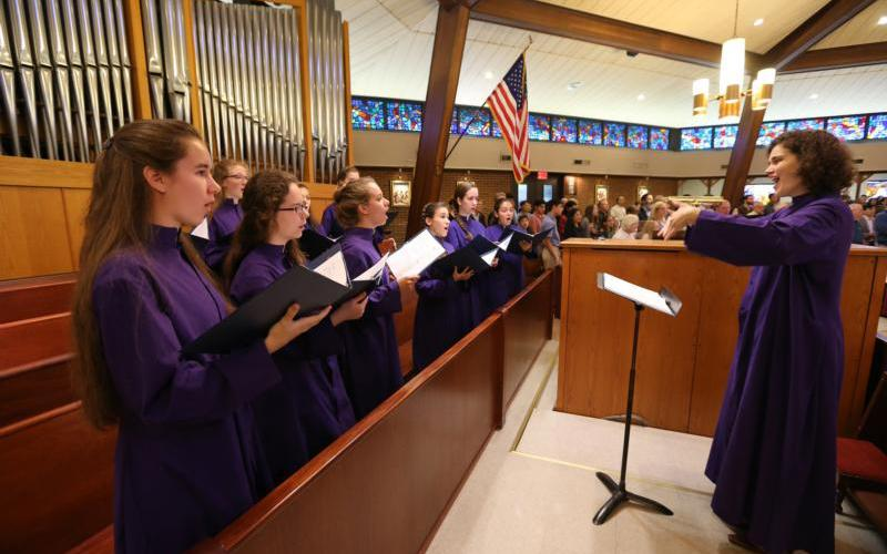 Elizabeth Black, assistant director of music at St. John the Beloved Church in McLean, Va., directs choir members as they sing Gregorian chant during a 2017 Mass. Choir members have to be committed. (CNS photo by Bob Roller)