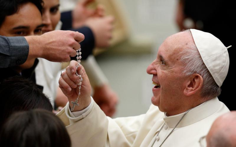 In this 2016 file photo, Pope Francis touches a rosary during his general audience in Paul VI hall at the Vatican. The rosary manages to be one of the easiest and the most difficult prayers of the Catholic Church. (CNS photo/Paul Haring)