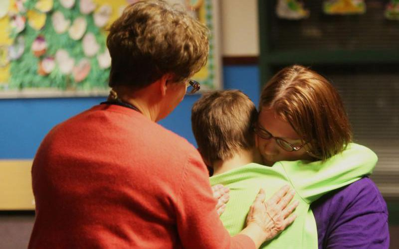 A boy is comforted during a session of Partners Around Loss through Support, or PALS, at Faithful Shepherd Catholic School in Eagan, Minn. (CNS photo by Dave Hrbacek/The Catholic Spirit)