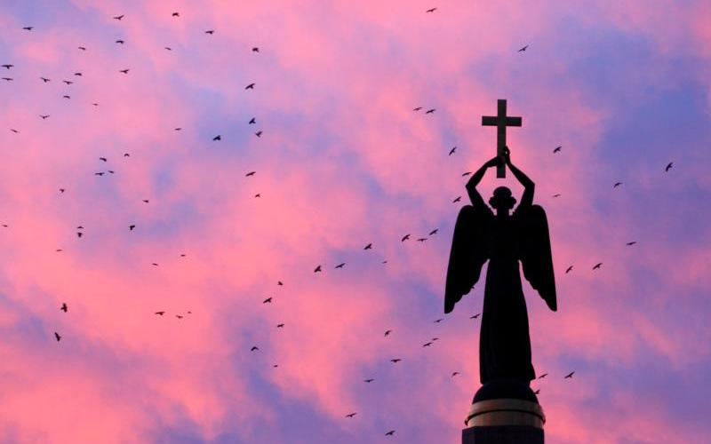 Birds fly near a statue of an angel holding a cross, the symbol of the city, at sunset in Stavropol, Russia, Nov. 5.