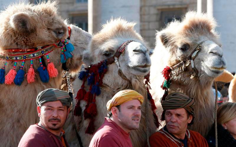 Three camels stand behind men in traditional attire in St. Peter's Square as Pope Francis leads the Angelus on the feast of the Epiphany at the Vatican. Many scholars believe that the Magi were priests of the Persian religion, men of high stature but definitely not kings, part of the account piously augmented in later centuries. (CNS photo by Paul Haring)