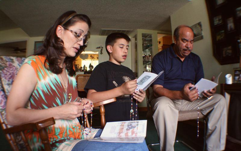 A family prays the rosary together in their Phoenix home. Along with prayer, spending time with the readings for each Sunday is a good practice, as is taking even one additional look at the readings from the past Sunday's liturgy. (CNS photo by J.D. Long-Garcia/The Catholic Sun)