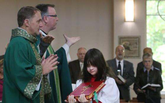 """Altar server Grace McGill carries the Book of Gospels as a priest gives the final blessing at the conclusion of Mass. At the end of Mass, we are blessed and sent """"in peace to love and serve the Lord."""" (CNS photo by Bob Roller"""
