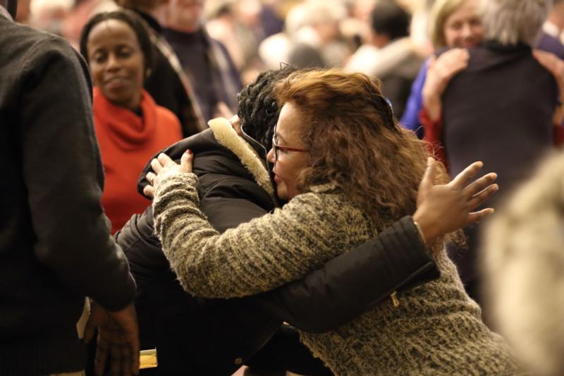 Women exchange the sign of peace during a solidarity Mass Jan. 31 at the Notre-Dame-de-Foy church in Quebec City.