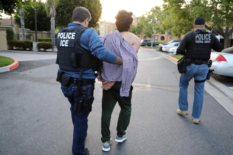 A U.S. Immigration and Customs Enforcement official arrests an Iranian immigrant in San Clemente, Calif., May 11.