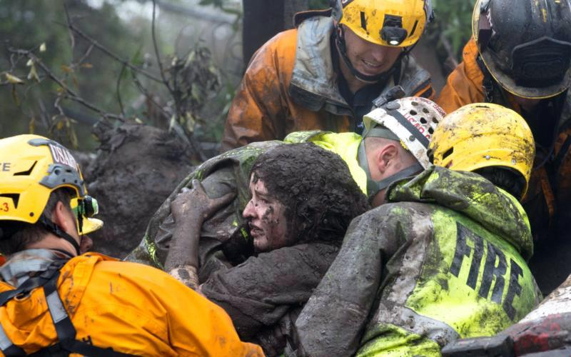 Emergency personnel carry a woman rescued from a collapsed house Jan. 9 after a mudslide in Montecito, Calif. Weeks after devastating fires tore through Southern California, heavy rains sent mudslides rolling down hillsides in Santa Barbara County, leaving at least 17 people dead and dozens injured.