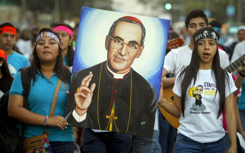"Salvadorans carry an image of Blessed Oscar Romero in 2016 in San Salvador, El Salvador, to commemorate the 38th anniversary his murder. During an April 11 homily in Washington, Salvadoran Archbishop Jose Luis Escobar Alas said the canonization of Blessed Romero will ""probably"" be in Rome and ""probably"" take place at end of October after a meeting of bishops. (CNS photo by Oscar Rivera/EPA)"