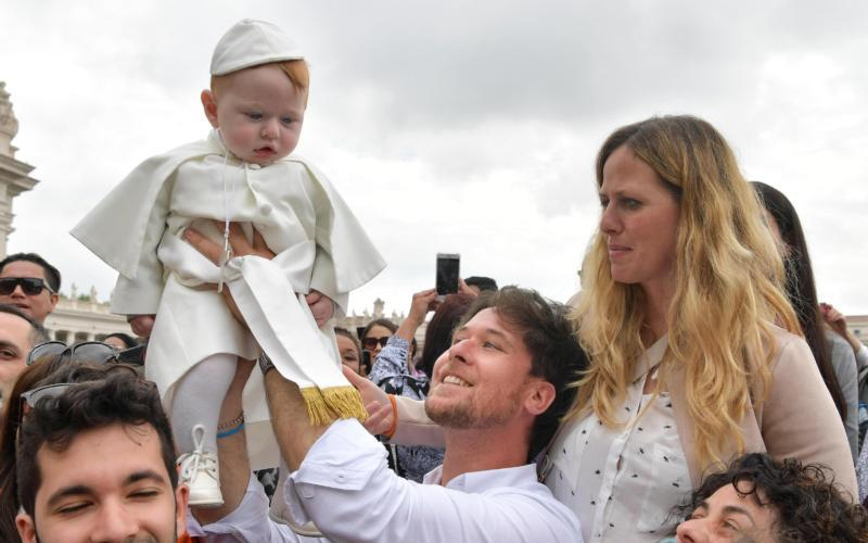 Parents lift a child wearing a pope outfit during the general audience in St. Peter's Square at the Vatican May 9. (CNS photo by Vatican Media via EPA)