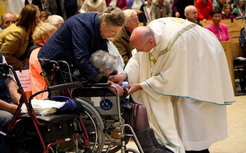 A priest blesses an elderly woman in 2017 at the Knock Shrine in Ireland. Pope Francis is scheduled to visit the shrine during his Aug. 25-26 trip to Ireland for World Meeting of Families in Dublin. (CNS photo courtesy John McElroy)