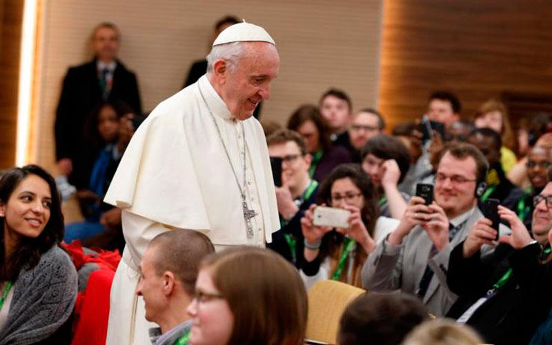 Pope Francis prepares to take a photo with young people at a presynod gathering of youth delegates in Rome March 19. The Vatican has released the working document for the October Synod of Bishops on young people, the faith and vocational discernment. (CNS photo by Paul Haring)