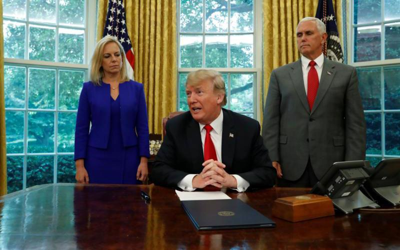 President Donald Trump is seen with with Secretary of Homeland Security Kirstjen Nielsen and Vice President Mike Pence at the White House June 20 prior to signing an executive order to halt the separation of families. (CNS photo by Leah Millis/Reuters)
