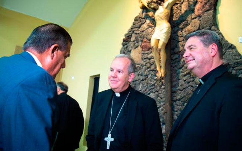 Bishop Joseph C. Bambera of Scranton, Pa., left, and Auxiliary Bishop Robert J. Brennan of Rockville Centre, N.Y., talk to a member of the media following a July 2 news conference at the Basilica of Our Lady of San Juan del Valle in San Juan, Texas. During the news conference, the bishops told reporters about the detention center for immigrants they visited earlier in the day in Brownsville, Texas. (CNS photo by Chaz Muth)