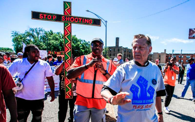 "Father Michael Pfleger, pastor of St. Sabina Parish in Chicago, leads the ""Dan Ryan Shut Down"" protest July 7 in Chicago. Father Pfleger and hundreds of anti-gun activists filled a major Chicago highway for about an hour demanding that city officials do something to stop gun violence in the city. (CNS photo by Tannen Maury/EPA)"