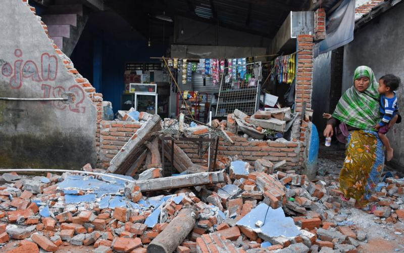 A woman walks past debris from a collapsed wall Aug. 6 following an earthquake on Lombok, Indonesia's popular tourist island. At least 91 people have been confirmed dead after the magnitude 7 earthquake Aug. 5, a week after another powerful quake killed more than a dozen people. (CNS photo by Ahmad Subaidi, Antara Foto via Reuters)