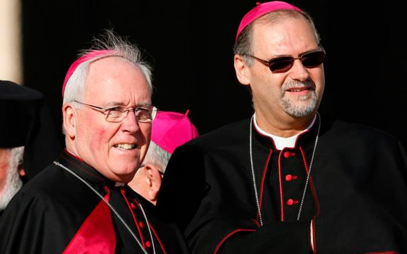 """Bishop Richard J. Malone of Buffalo, N.Y., left, is pictured with another prelate in St. Peter's Square in 2014 at the Vatican. The bishop recommitted Aug. 26 to serving the diocese despite calls for his resignation over the handling of priests accused of sexual abuse. """"The shepherd does not desert the flock at a difficult time,"""" he said. (CNS photo by Paul Haring)"""