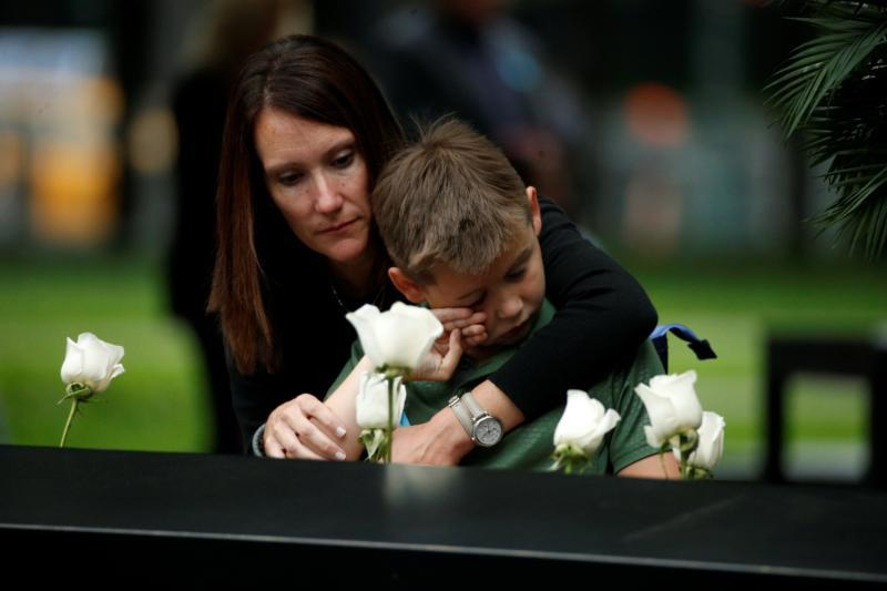 A woman and child place flowers at the National September 11 Memorial and Museum during Sept. 11 ceremonies to mark the 17th anniversary of the terrorist attacks in New York. Nearly 3,000 people died in the attacks in New York City and Shanksville, Pa., and at the Pentagon. (CNS photo by Brendan McDermid/Reuters)