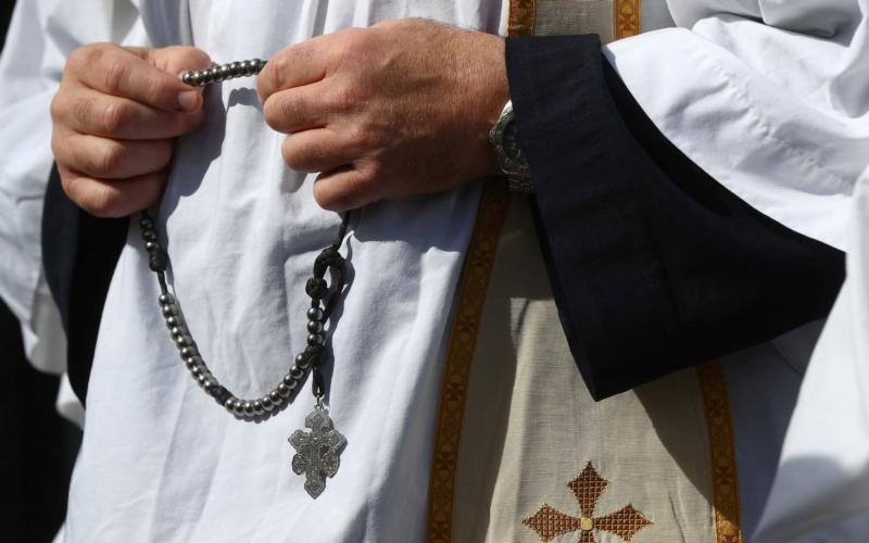 A priest holds a rosary Aug. 24 outside the Pastoral Congress at the World Meeting of Families in Dublin. (CNS photo by Hannah McKay/Reuters)