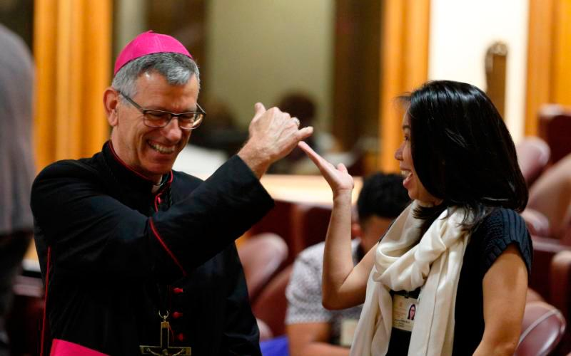 Auxiliary Bishop Mark Stuart Edwards of Melbourne, Australia, shares a laugh with Indonesian youth delegate Anastasia Indrawan before a session of the Synod of Bishops on young people, the faith and vocational discernment at the Vatican Oct. 9. (CNS photo by Paul Haring)