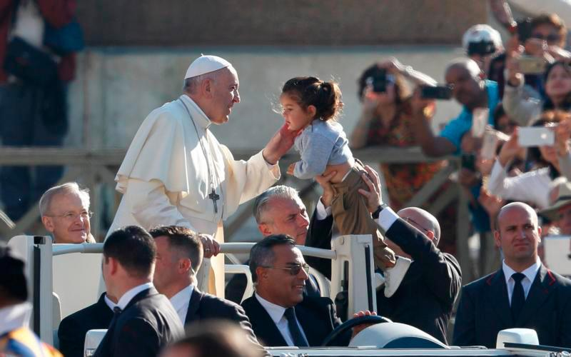 Pope Francis greets a child during his general audience in St. Peter's Square at the Vatican Oct. 10. (CNS photo by Paul Haring)