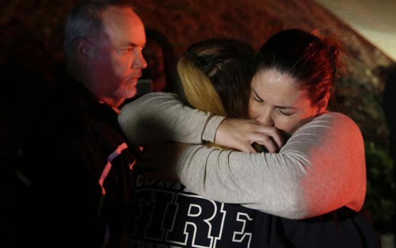 A woman who fled the Borderline Bar and Grill is embraced by a first responder Nov. 8 after a gunman killed at least 13 people. The gunman, who opened fire without warning late Nov. 7, was found dead inside the establishment, authorities said. (CNS photo by Mike Nelson/EPA)