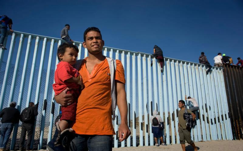 Oscar Ruiz, 22, and his son Jesser Ruiz, 1, stand next to the U.S.-Mexico border fence Nov. 13 after arriving in Tijuana with a group of about 350 Central Americans. The group split from and advanced ahead of a larger caravan making its way to the border. (CNS photo by David Maung)