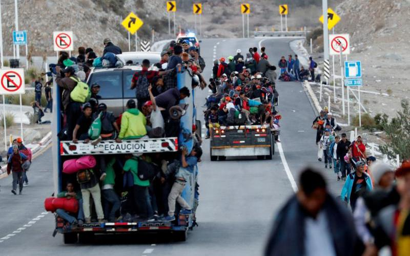 Migrants from Central America, part of the migrant caravan traveling to the U.S., ride in trucks Nov. 20 in Mexicali, Mexico. (CNS photo by Kim Kyung-Hoon/Reuters)