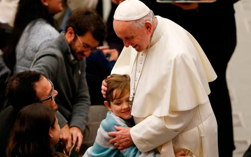 A boy embraces Pope Francis during his general audience in Paul VI hall at the Vatican Jan. 9. (CNS photo by Paul Haring)