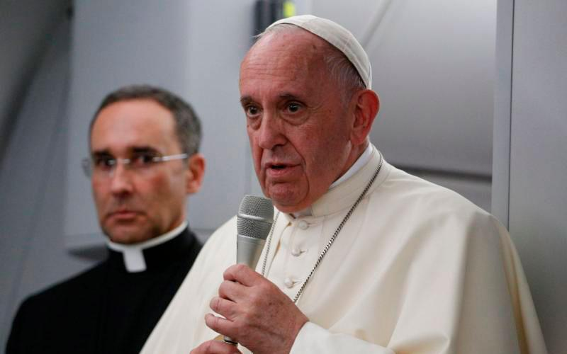 Pope Francis answers questions from journalists aboard his flight from Panama City to Rome, Jan. 27, 2019. Also pictured is Msgr. Mauricio Rueda, papal trip planner. (CNS photo by Paul Haring)