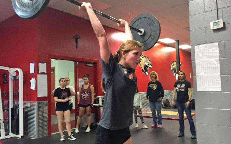 Grace Dickinson, a senior at Cardinal Mooney High School in Sarasota, Fla., performs a dead lift to an overhead press with 95 pounds as her coaches observe her Dec. 19, 2018. This is the inaugural year for the girls weightlifting team at the Florida Catholic school. (CNS photo by Jean Gonzalez/Florida Catholic)