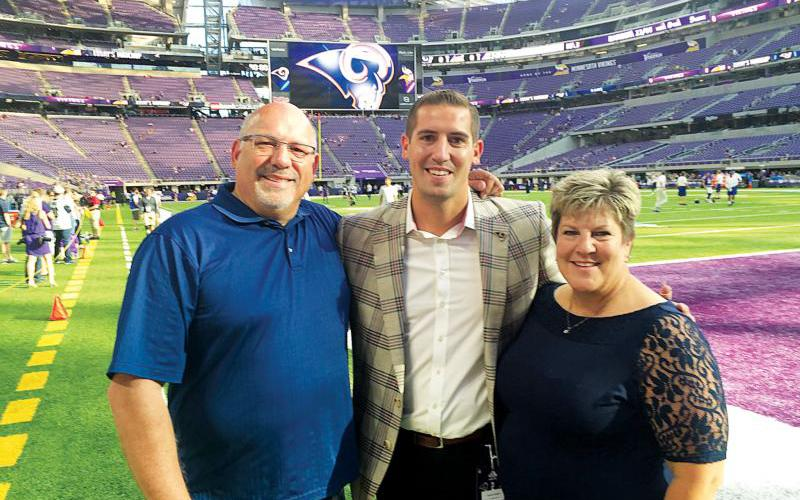 Tony Pastoors, center, poses on the field at U.S. Bank Stadium in Minneapolis with his parents, Pat and Betsy, in 2017 when the Los Angeles Rams played the Minnesota Vikings. (CNS photo courtesy the Pastoors Family)