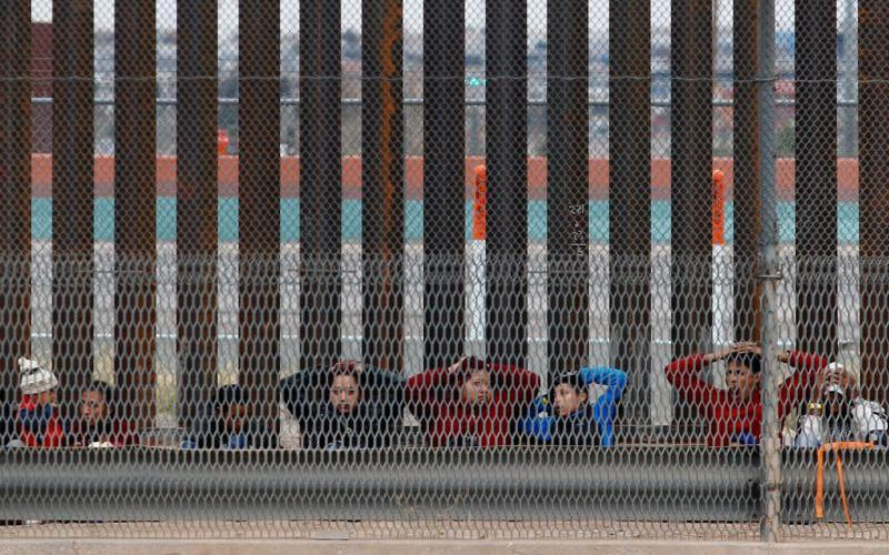 Migrants from Central America are being escorted by U.S. Customs and Border Protection officials after crossing the border from Mexico to surrender to the officials in El Paso, Texas, in this picture taken from Ciudad Juarez, Mexico, Feb.10, 2019. (CNS photo by Jose Luis Gonzalez/Reuters)