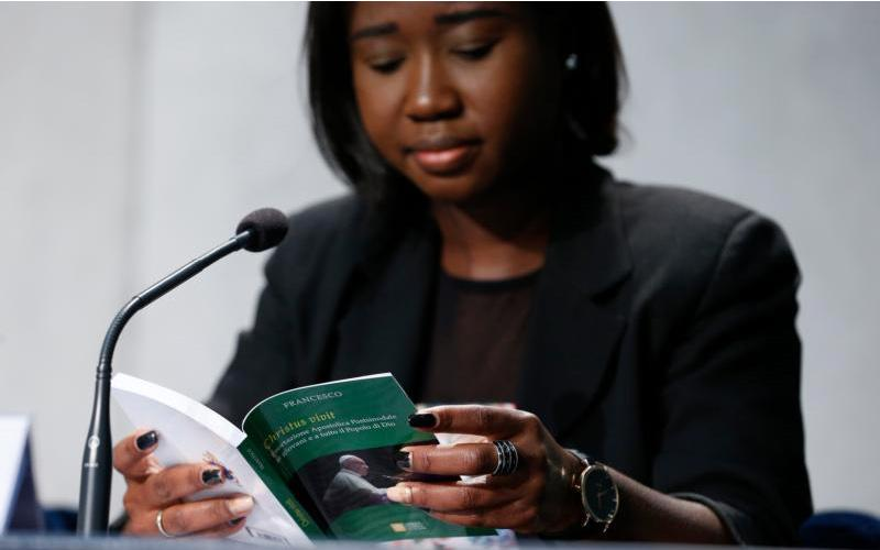 "Laphidil Oppong Twumasi, a youth leader from Ghana, reads Pope Francis' apostolic exhortation, ""Christus Vivit"" (Christ Lives), during a news conference for its presentation at the Vatican April 2, 2019. (CNS photo by Paul Haring)"
