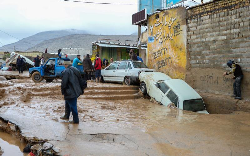 People walk near damaged vehicles after flooding in Shiraz, Iran, March 26, 2019. Pope Francis has sent a donation to assist tens of thousands of Iranians who lost their homes and businesses in waves of severe flooding that began in mid-March. (CNS photo/Tasnim News Agency via Reuters)