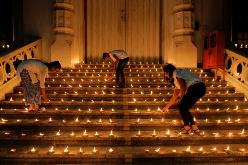 Young people light candles near the closed door of a church in Colombo, Sri Lanka, April 28, 2019, during a vigil in memory of the victims of a string of suicide bomb attacks across the island on Easter . (CNS photo by Thomas Peter/Reuters)
