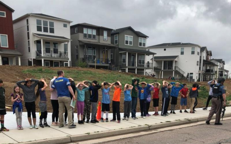 School children stand in line with an armed police officer near STEM School Highlands Ranch during a shooting incident at the Colorado school May 7, 2019. (CNS photo by Shreya Nallapati/social media via Reuters)