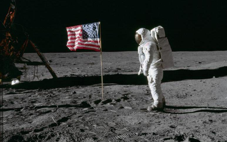 """Astronaut Edwin """"Buzz"""" Aldrin, lunar module pilot of the first lunar landing mission, poses for a photograph beside the deployed U.S. flag during an Apollo 11 extra-vehicular activity on the lunar surface July 20, 1969. (CNS photo courtesy NASA)"""