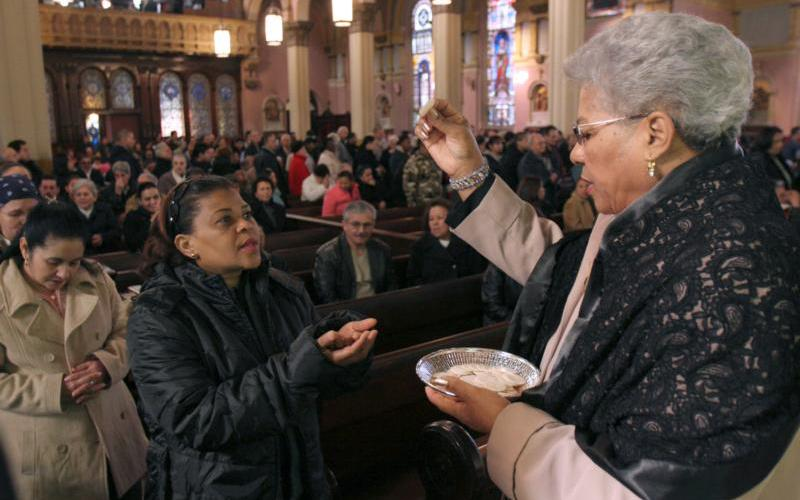An extraordinary minister of holy Communion in Brooklyn, N.Y., distributes the Eucharist during Mass in this 2008 file photo.