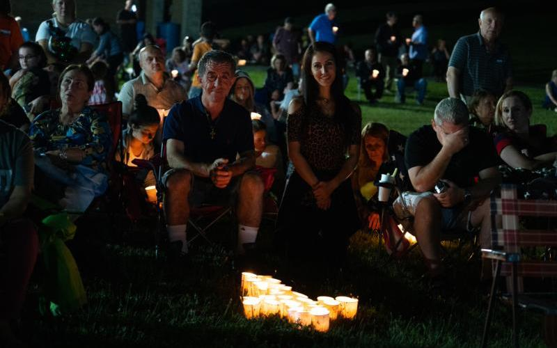 Chaldean Catholics Khalid Markos and his daughter, Lina Markos, participate in a vigil Mass outside the Basilica and National Shrine of Our Lady of Consolation in Carey Aug.14, 2019.