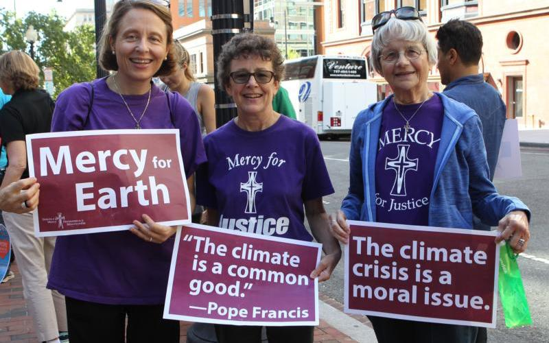 Mercy Sister Aine O'Connor, Marianne Comfort, justice coordinator for the Mercy Sisters, and Mercy Sister Rita Parks, all from Silver Spring, Md., hold aloft signs Sept. 20, 2019, in front of St. Patrick's Church in Washington as they prepare to join the climate change march.