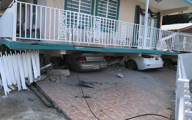 Cars lie under a collapsed house after an earthquake in Guanica, Puerto Rico, Jan. 6, 2020.