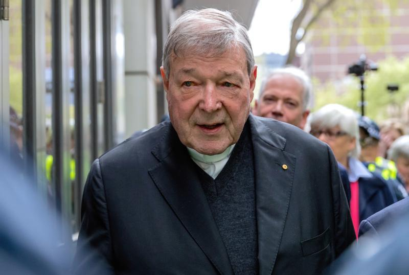 Australian Cardinal George Pell is surrounded by police as he leaves the Melbourne Magistrates Court in Australia, Oct. 6, 2017.
