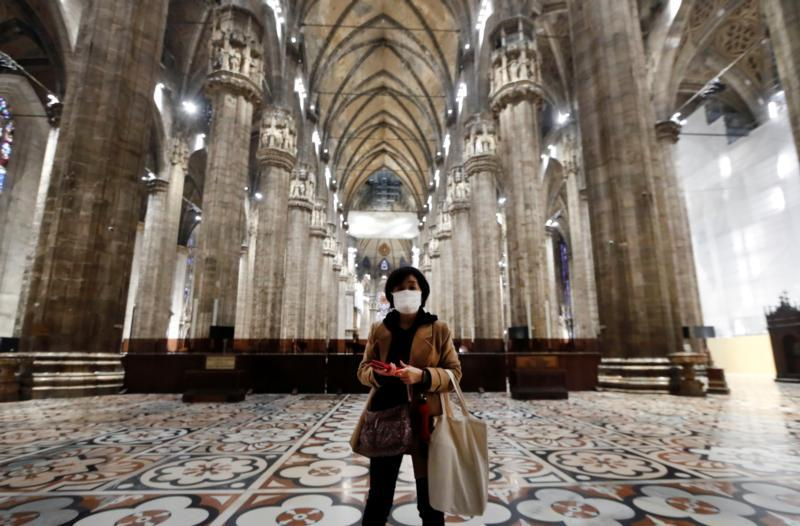 """A tourist wearing a protective mask visits Milan's famed cathedral, commonly referred to as the """"Duomo,"""" as it reopened to the public for the first time since the coronavirus outbreak March 2, 2020."""