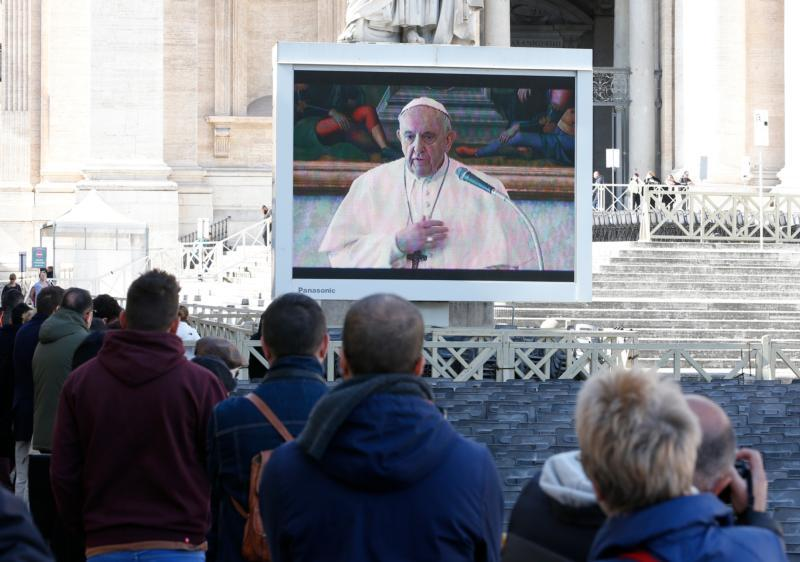 Pope Francis is pictured on a video monitor in St. Peter's Square as he leads the Angelus from his library in the Apostolic Palace at the Vatican March 8, 2020